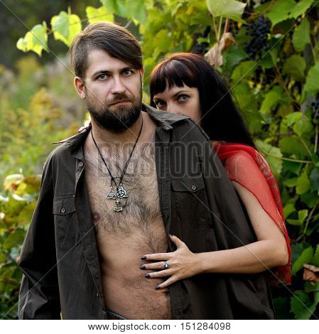 Half naked man and woman portrait in wild grapes