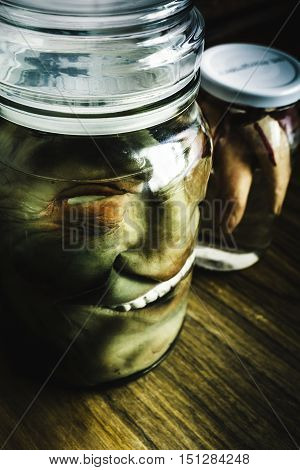 Scary preserved halloween decorations with a monster head and hand in vinegar jars. Pickled horror heads