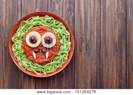 Green spaghetti pasta spooky halloween vegetarian food vampire monster with smile, fake blood tomato sauce and funny big mozzarella eyeballs decoration kid party meal on vintage table