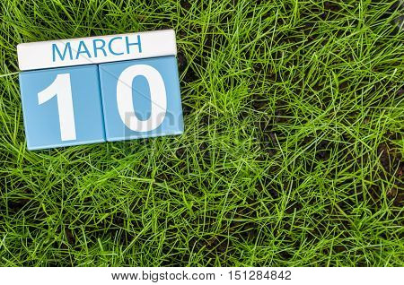 March 10th. Day 10 of month, calendar on football green grass background. Spring time, empty space for text.