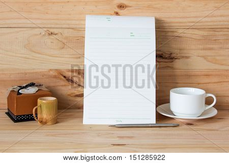 Note book with coffee cup on wood