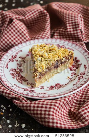 Piece of peanut butter pie with strawberry jam and peanuts on a plate, selective focus