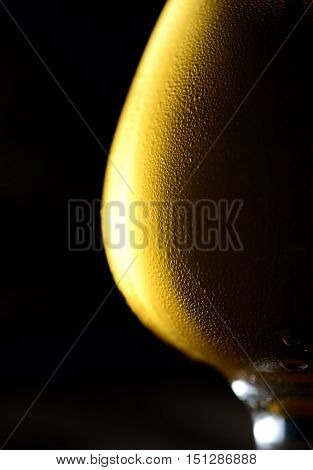 The cold frothy beer in a glass of original color on a black background
