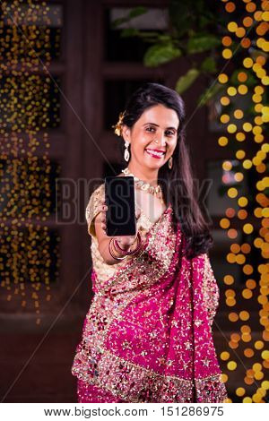 Young indian smart girl or lady showing smart phone screen against diwali lighting  background. indian woman celebrating diwali with smartphone showing blank screen