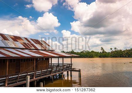 Wooden vintage style stilt house built above river Bangprakong rural Thailand.