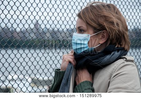 Portrait of woman walking on the street wearing protective mask as protection against infectious diseases.