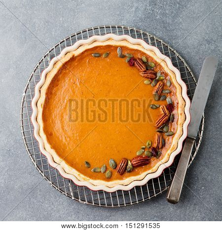 Pumpkin pie, tart made for Thanksgiving day. Grey stone background. Top view
