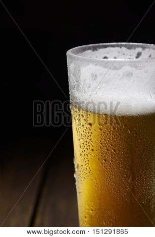 The cold frothy beer in a glass on a black background