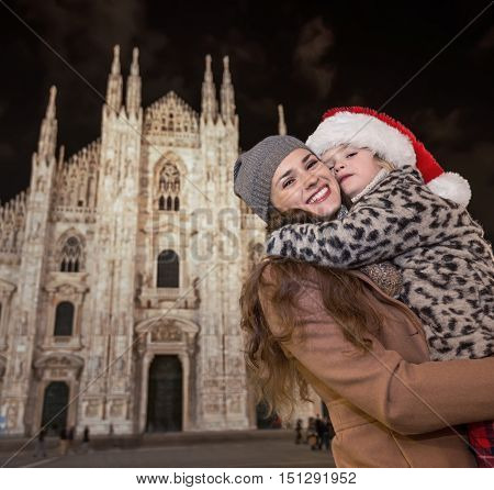 Mother And Child In Christmas Hat In Front Of Duomo Hugging