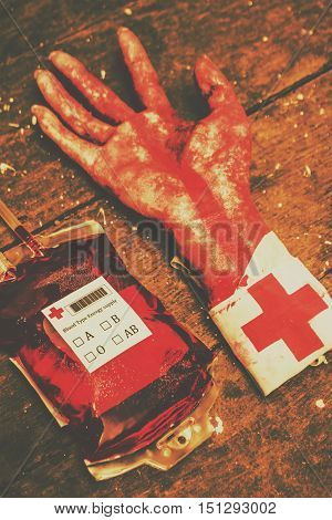 Halloween Horror Hospital Still Life of a Bag of Blood and Severed Hand with Red Cross Bandage on Wrist Resting on Rustic Wooden Table