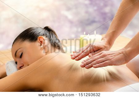 Close up conceptual alternative therapy portrait of attractive woman. Therapist working with hands on back with light beam.