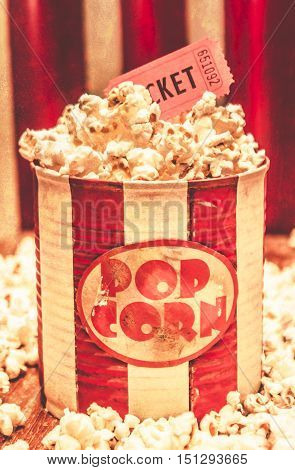 Vintage red and white striped tub of freshly made buttery salted popcorn overflowing onto the table in front of stage curtain with a old ticket stub. Retro entertainment