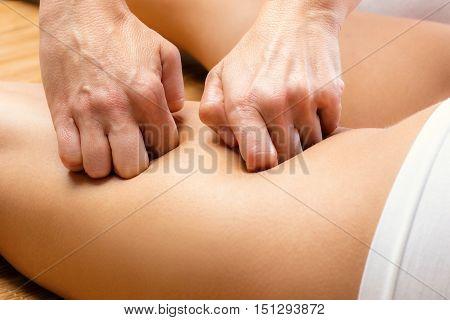 Close up Detail of hands massaging female hamstring.
