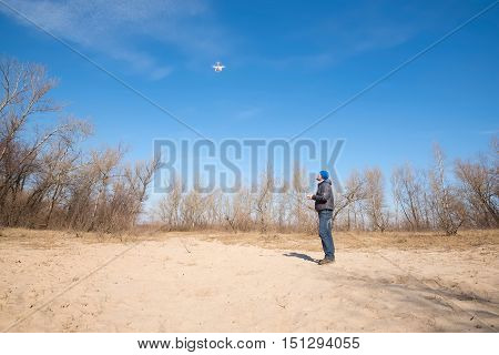 Man controls drone on the autumn beach. Wide angle.