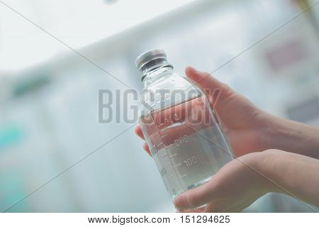 Medicine bottle in hands of health worker.