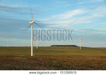 Wind turbines in open farmland against a cloudy sky turning in the wind