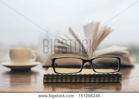 Closeup of glasses coffee cup spiral notepad and book