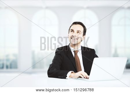 Happy young businessman daydreaming at white workplace with laptop. Success concept