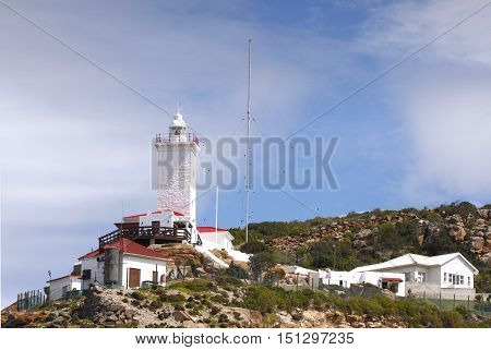 Lighthouse placed on the side of a mountain to help guide ships away from a rocky reef in the sea