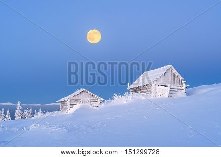 Winter landscape with old wooden hut in a mountain village. Morning twilight with a full moon and clear blue sky. Fresh snow and frost on the walls and roofs of houses