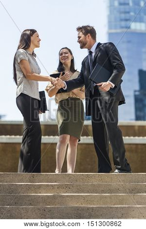 Multiracial business team of successful man and women, businessman businesswoman, meeting celebrating shaking hands in a modern city