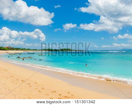 Beautiful white sand beach surrounded by tropical palm trees on the island of Bali in Nusa Dua area. Blue sky with white clouds white sand and palm trees.