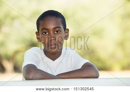 Serious Boy With Folded Arms At Table