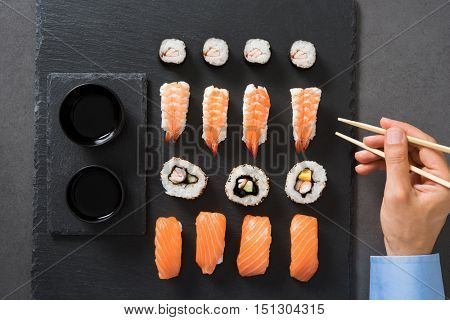 Top view of man eating sushi roll with chopsticks at restaurant. Close up of hand holding chopstick to eat japanese food. High angle view of young businessman eating sushi served on a black plate.