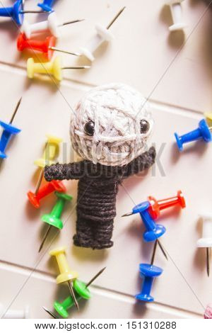 Handmade sting voodoo doll laying amongst scatter of pins and needles. Modern black magic