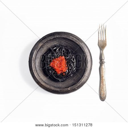 black pasta with red caviar on a white background