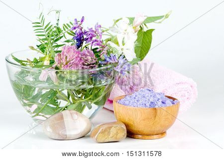Spa setting with flowers and lilac bath salts