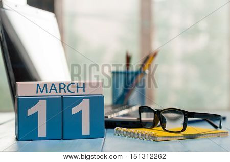 March 11th. Day 11 of month, calendar on business office background, workplace with laptop and glasses. Spring time, empty space for text.