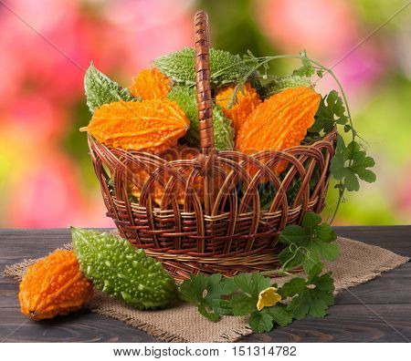 bitter melon or momordica in a wicker basket on wooden table with blurred background.