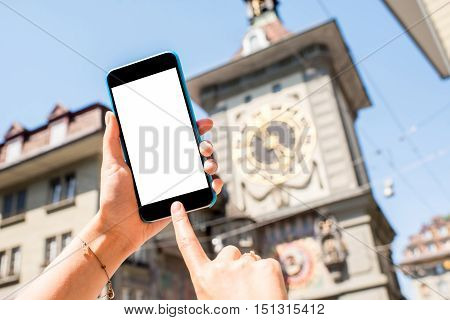 Holding a smart phone with white screen with a famous clock tower on the background in the old town of Bern city in Switzerland