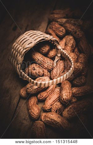Peanuts scattered on wooden ground with tiny wattled basket. Still-life food art