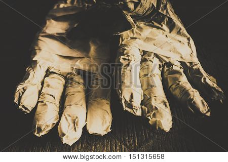 Satanic image of cursed mummified hands emerging from coffin mummy hands in bandage horror halloween concept