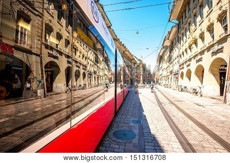 Bern, Switzerland - June 24, 2016: Street view on Kramgasse with red tram in the old town of Bern city. Kramgasse is a popular shopping street and medieval city centre of Bern, Switzerland