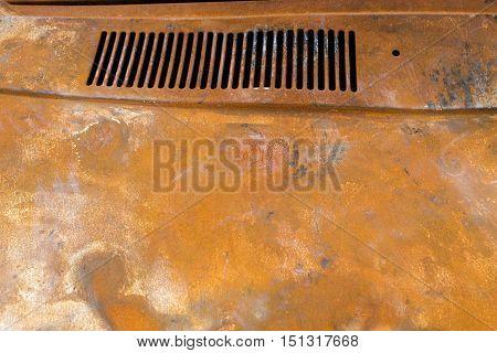 Rusty metal hood of the burnt car.