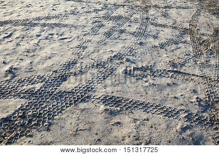 Wheel tracks on the wet sand after the rain