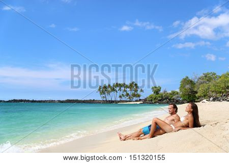 Beach vacation relaxation. Happy couple relaxing sunbathing lying down on sand together tanning under the tropical sun in getaway travel destination. Young adults enjoying their holidays.