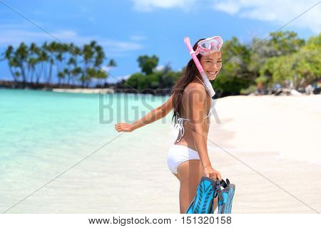 Happy beach vacation girl having fun doing snorkel watersport activity in caribbean ocean. Asian woman enjoying swimming in tropical destination vacation travel on perfect beach.