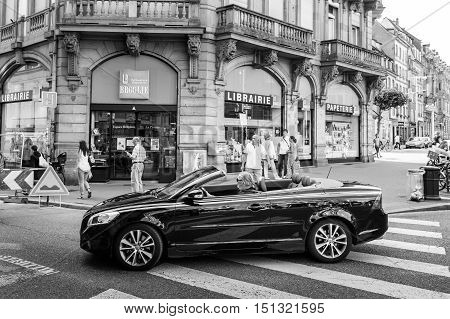 Black and white view of senior man driving beautiful Volvo C70 Convertible car crossing pedestrian walk in the center of the French city of Strasbourg Alsace on a summer day with pedestrians and tourists
