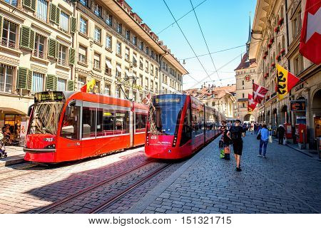 Bern, Switzerland - June 24, 2016: Street view on Marktgasse with red tram and people walk in the old town of Bern city in Switzerland.