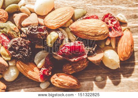 Trail mix high-energy snack food background with a nutritious mixture of nuts seeds kernels dried fruit and chocolate on a wooden surface in a close up view