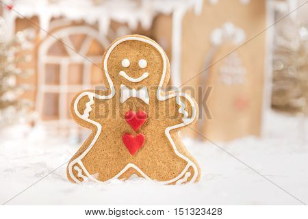 Gingerbread man cookie standing in front of a gingerbread house.