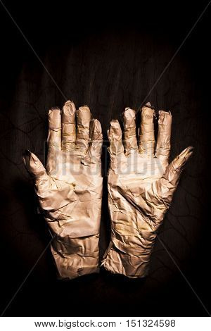 Scary mummy's hands showing scary halloween copyspace on dark wooden background