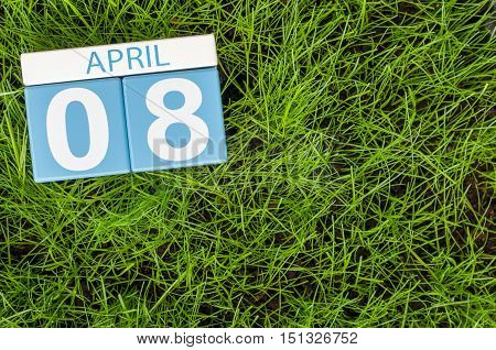 April 8th. Day 8 of month, calendar on football green grass background. Empty space for text.