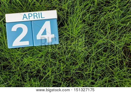 April 24th. Day 24 of month, calendar on football green grass background. Spring time, empty space for text.