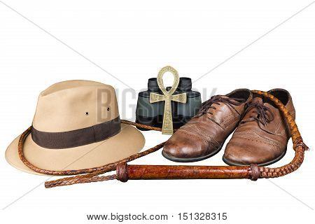 Travel and adventure concept. Vintage brown shoes with fedora hat, bullwhip, binoculars and key of life ankh isolated on white background
