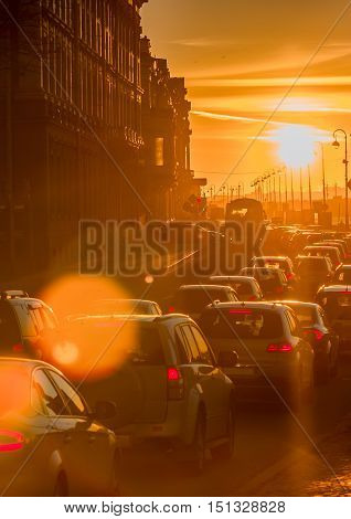 Cars are in a traffic jam during a beautiful golden sunset in a big sity.